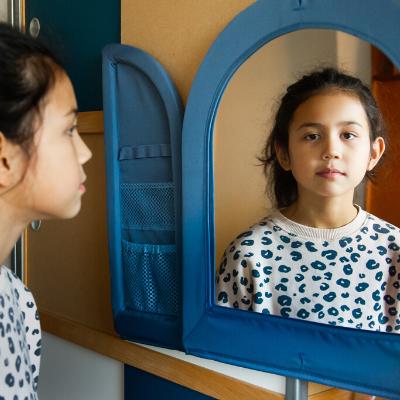 Meisje dat in een spiegel kijkt