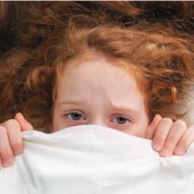 Bang meisje met laken deels over haar gezicht getrokken